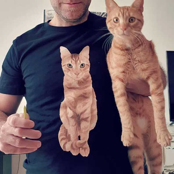 A picture of an owner who is wearing a T-shirt with a picture of his cat