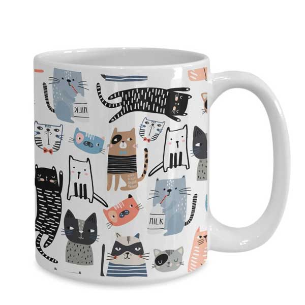 A coffee or tea mug with many colorful cats on Etsy