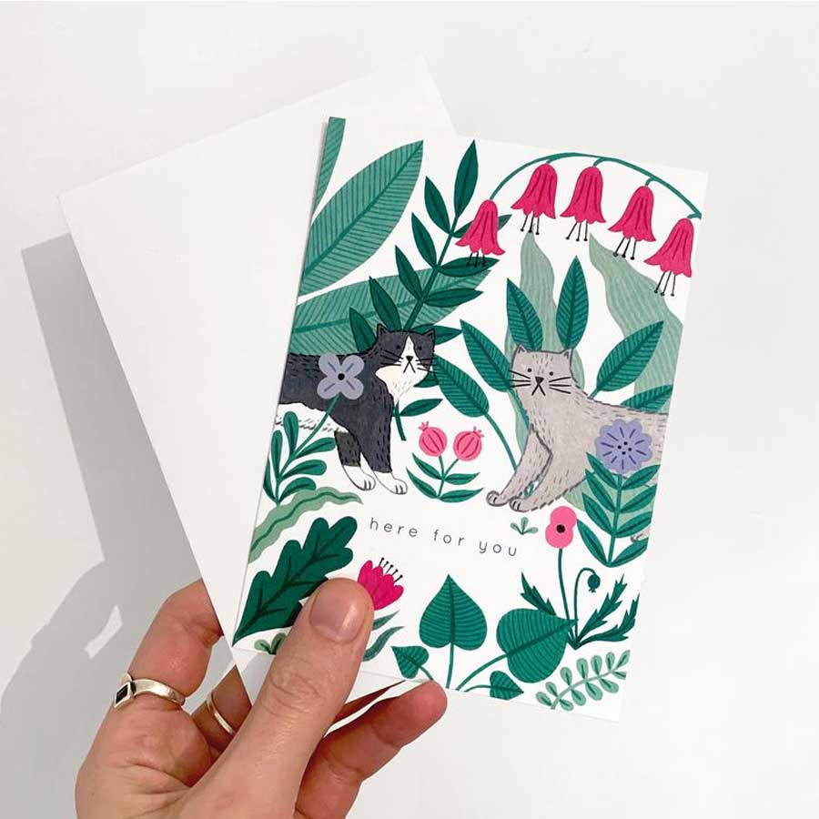 A cat loss card with a black and white cat and a grey kitty with flowers and green leaves