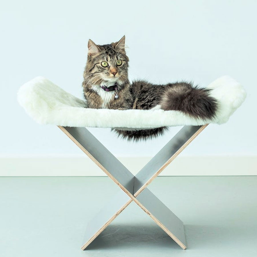 a cat is lying on a cat hammock with faux fur