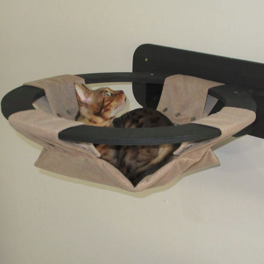 a small kitten is lying on wall mounted cat bed made from canva