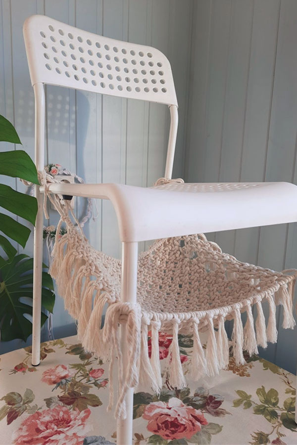 A simple macrame cat hammock under the white chair