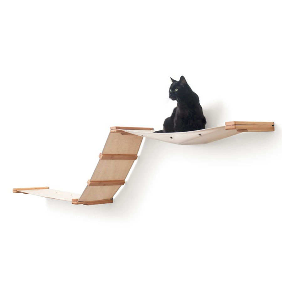 a black cat is lying on wall mounted cat hammock