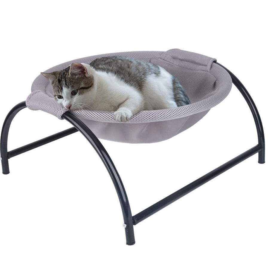 A white and grey kitty who is lying on grey floor cat hammock