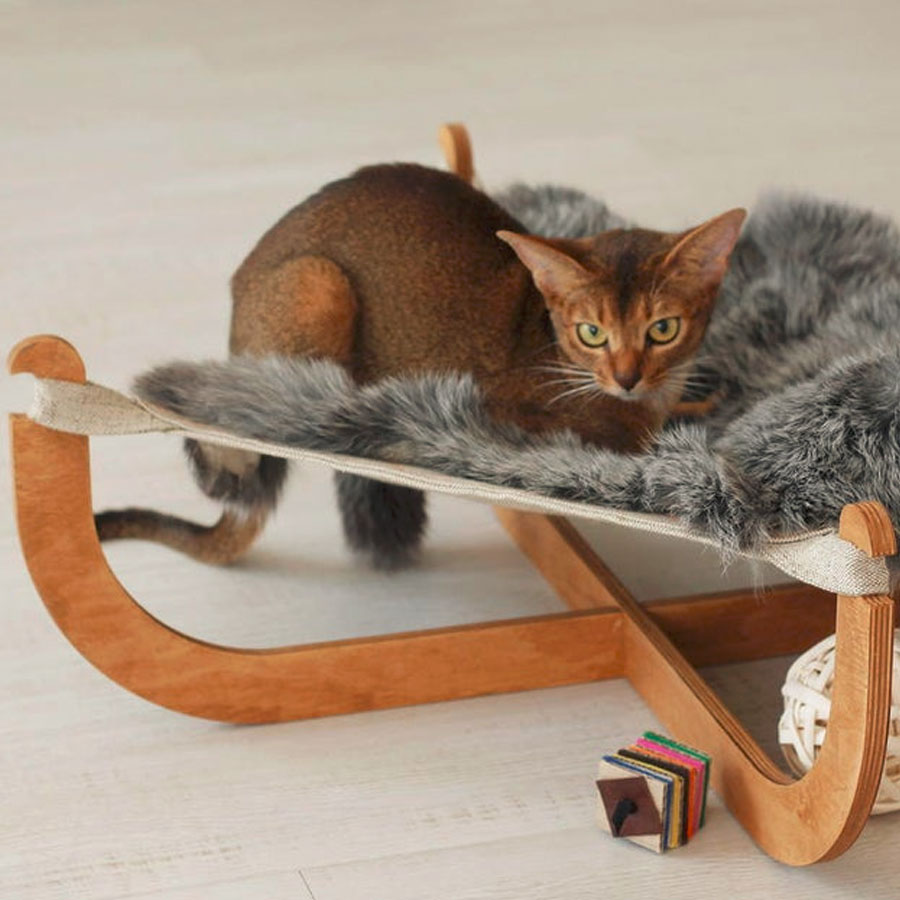 A beautiful wooden hammock by CatPlayFurniture with a kitty lying on it
