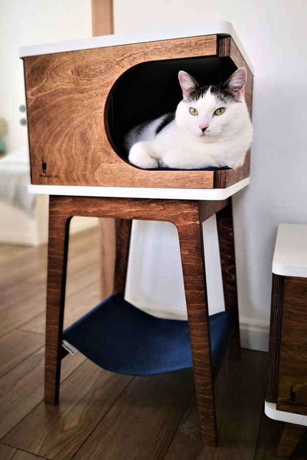 A retro cat bed with a hammock and a white cat inside the house