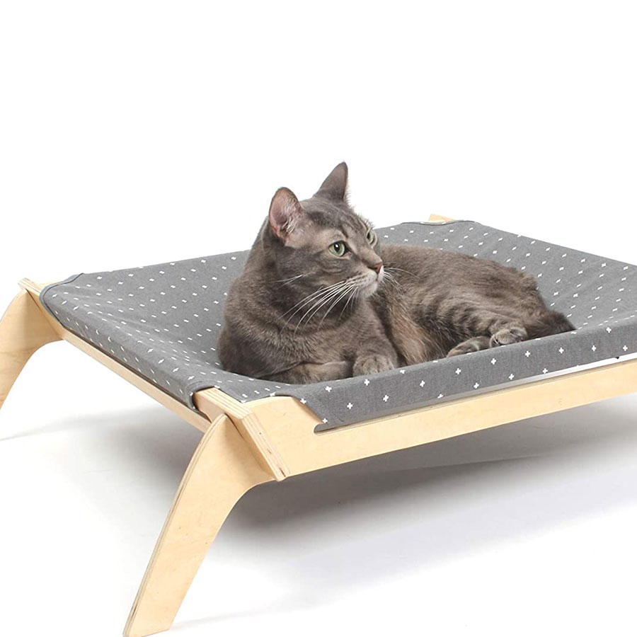 a grey cat is lying on a simple cat hammock