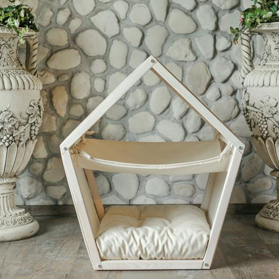 A small white wooden house with a hammock for cats