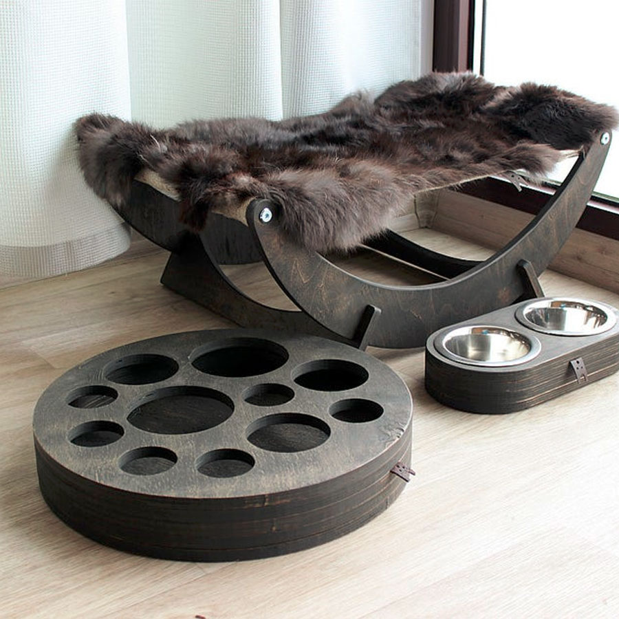 A luxurious wooden cat hammock with bowls and toys