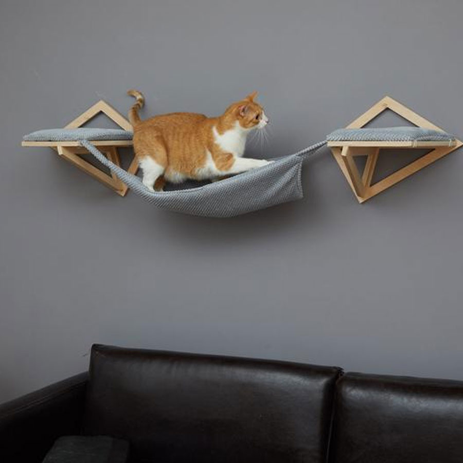A white and ginger cat is walking on grey wall mounted cat hammock