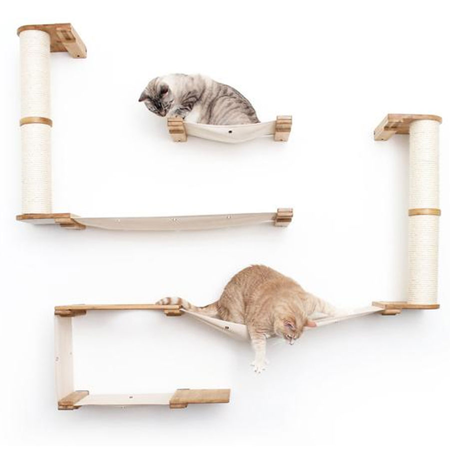 two ginger cats hanging on wall mounted shelves with a hammock