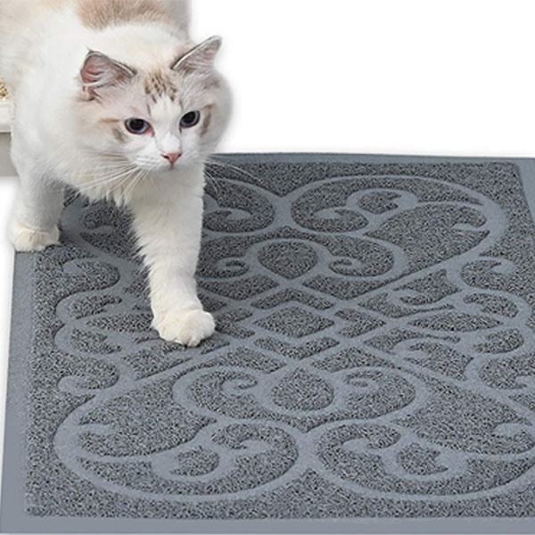 a white kitty is walking on grey cat litter mat